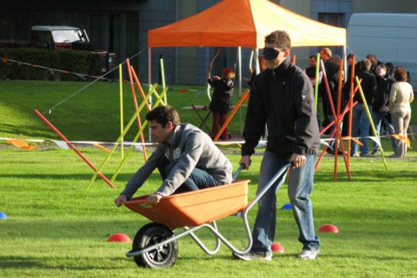 Two men blindfold wheel barrow racing during Duke of Leinster Games