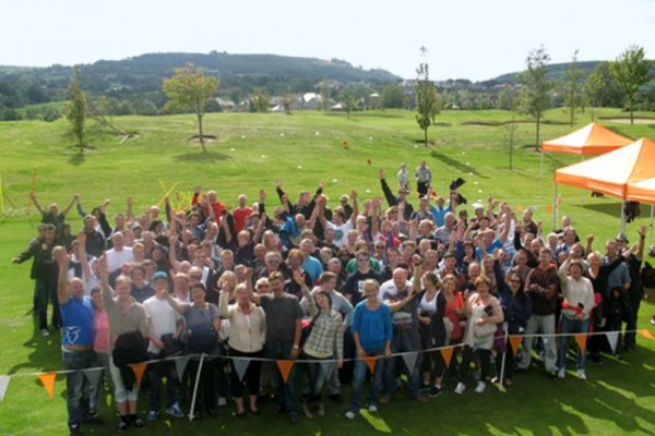 Happy group of delegates cheering all together after their outdoor team building corporate away day with Orangeworks.