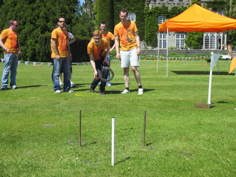 Delegates wearing orange T-shirts taking part in horseshoe throwing as part of their Irish themed corporate sports day.