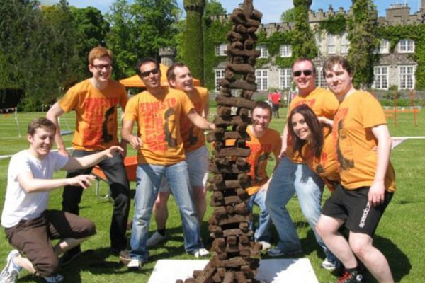 Delegates smile next to their giant stack of turf that they created during their Irish themed corporate sports day.
