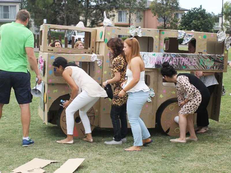 Everyone smiling and cheering in front of the cardboard buses they created during their outdoor team development program.