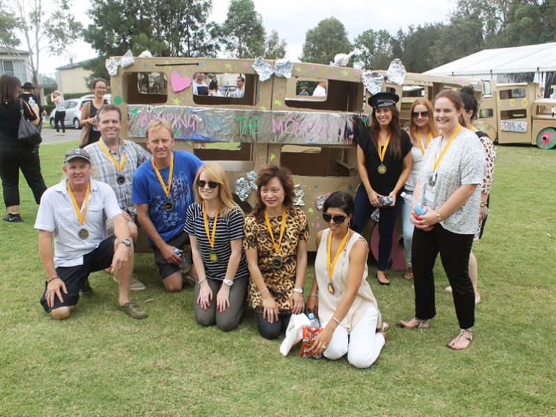 Winning delegates wearing their medals and smiling next to the cardboard bus they created during their corporate day out.