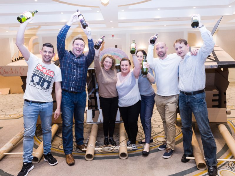 Winning team smiling with their prize of a bottle of wine, after they completed their team development day with Orangeworks.