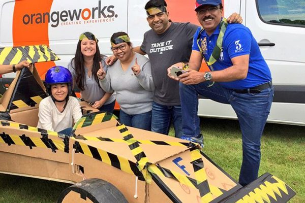 Delegates smiling with their formula 1 car before racing