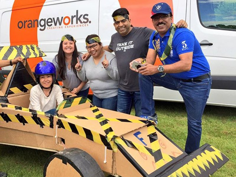 Delegates smiling with the cardboard formula one car they built during their fun team building experience.