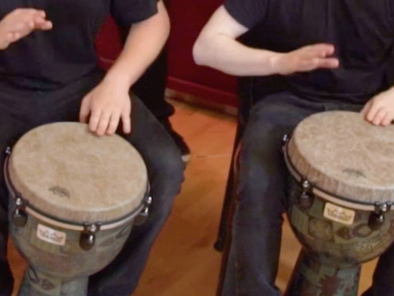 Two delegates playing the drums during Global Grooves, a samba drumming style team building activity by Orangeworks.