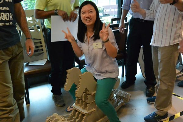 A delegate sitting on the newly created cardboard horse in Horses for Causes