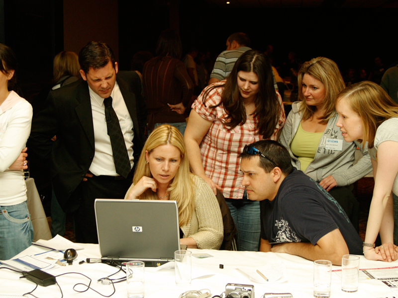 Delegates working on their news piece during Making the News, an Orangeworks indoor team building exercise.