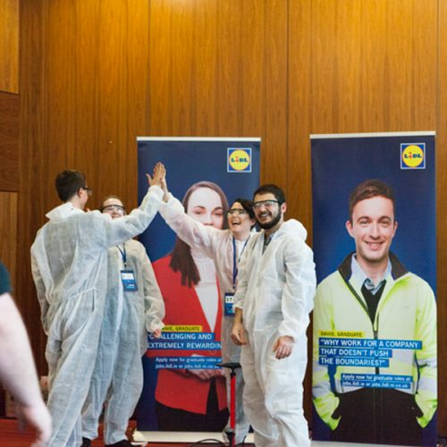 Delegates wearing white overalls, smiling and cheering as they completed Beat the Box, a fun team building challenge.