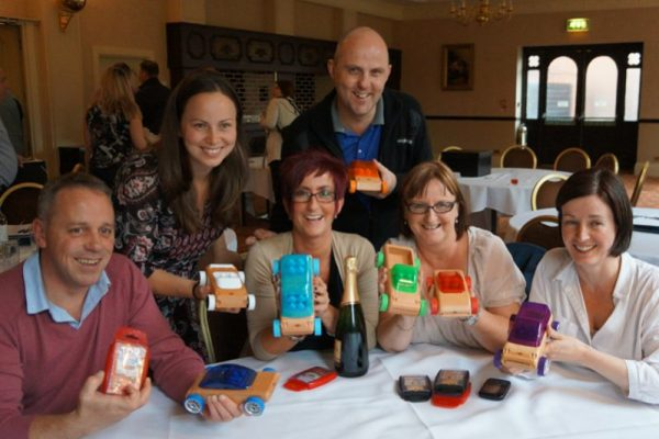 The winning team of Need 4 Speed, a charity based corporate activity, smile with their prize and their creations.