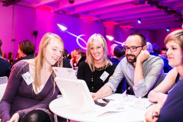 Team working together looking at an Ipad during Push It, the company event by Orangeworks.
