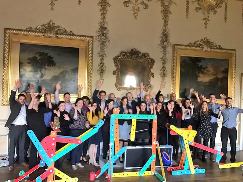 Delegates smiling with their hands in the air with their Rat Trap contraption they created during their company away day.