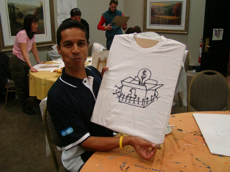 A delegate smiling with their newly designed t-shirt during Tshirt Masterpiece a staff bonding challenge by Orangeworks.