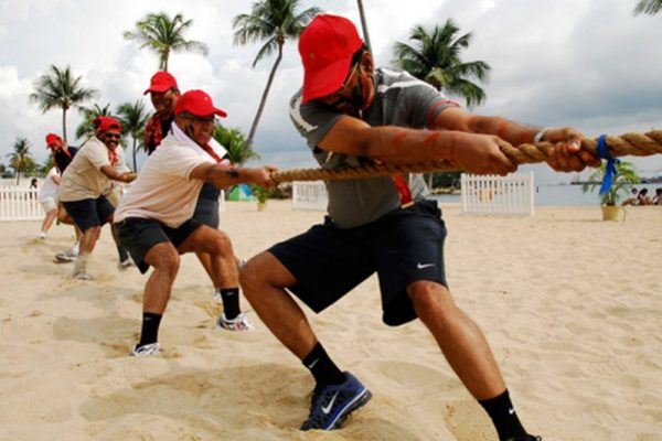 Delegates wearing red capes pulling a rope during Tug of War, one of the team challenges completed during Two Tribes.
