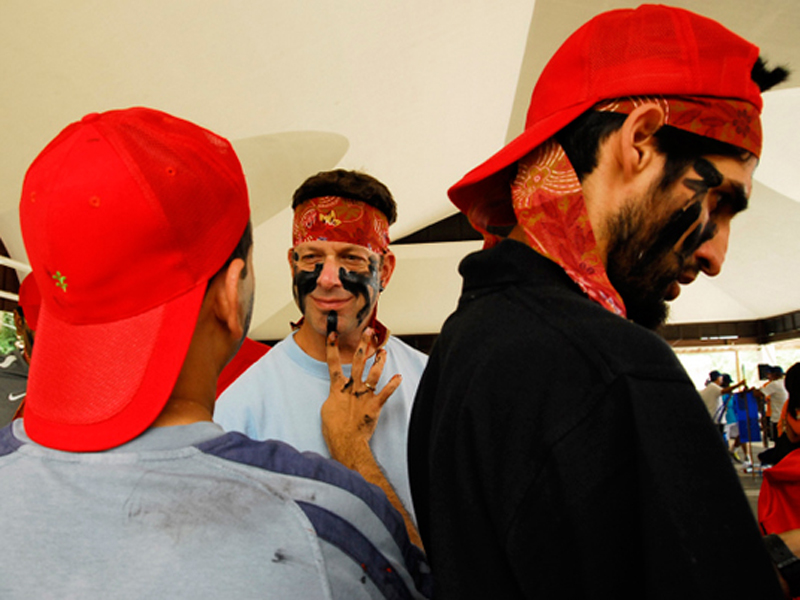 Delegates wearing red caps & putting face paint on as they prepare for Two Tribes, an Orangeworks outdoor team building event