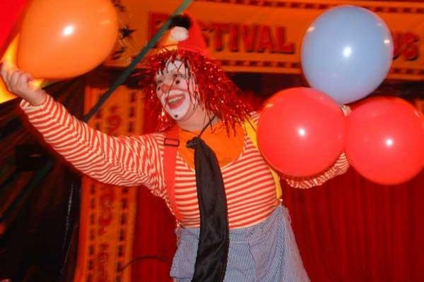 Laughing clown with balloons during Urban Circus, a corporate evening experience hosted by Orangeworks.