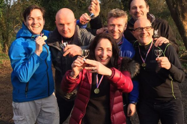 Winning team smiling with their trophies after winning Xtreme Forest Adventure, an outdoor team building challenge.