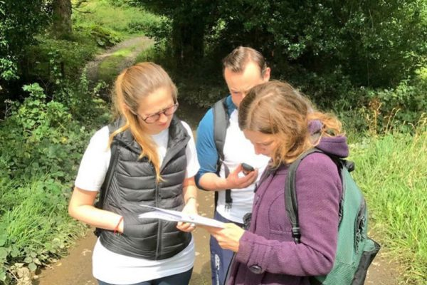 Delegates working together during an Orangeworks outdoor team activity, using their GPS to find the next Go Team challenge.