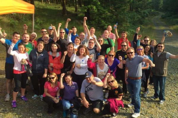 Team smiling after completing Xtreme Forest Adventure, an Orangeworks activity that tests your outdoor survival skills.