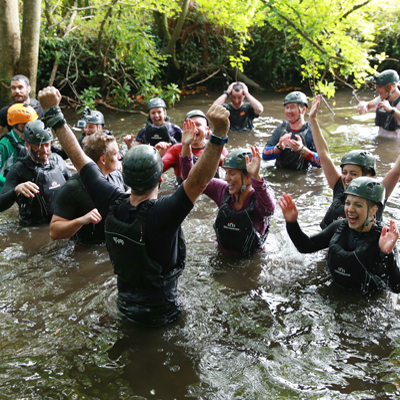 Delegates cheering in the water as they have completed their Bear Grylls Survival Academy with Orangeworks.