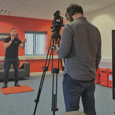 A cameraman looking into his camera lens as he is filming Dean, one of Orangeworks beatboxers, for a promotional video.