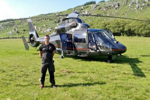 Our Operations Director, Will, next to a helicopter during one of Orangeworks bespoke adventure team activities.
