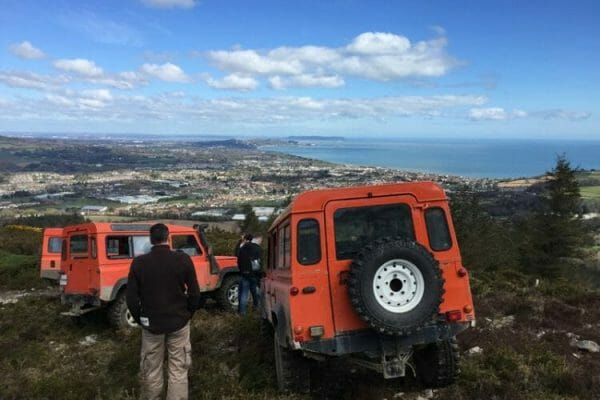 Delegates with our Orange Land Rover Defenders during Mountain Mixology, a fun bespoke team building activity.