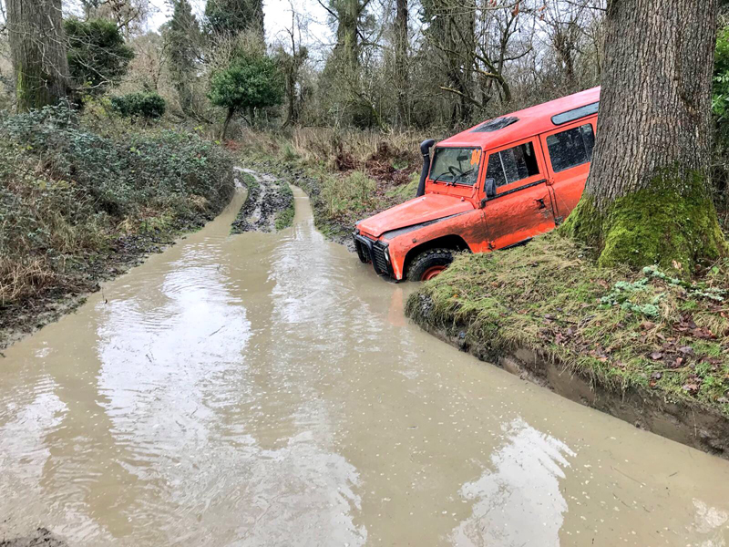 Orange landrover driving through a stream during the orangeworks 4x4 Off Road Driving course at Carton House.