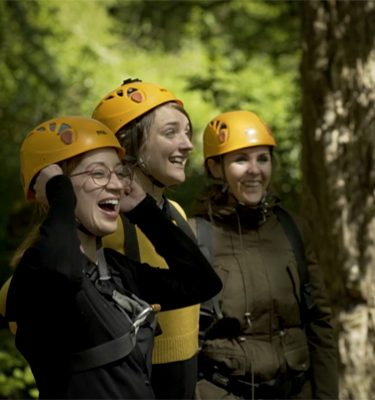Delegates cheering wearing helmets ready for Altitude High Ropes at Carton House.