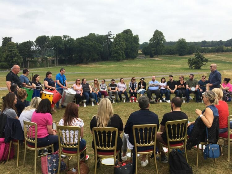 Delegates sitting outside Slane Castle in a circle ready for Beatswork, their team building challenge.