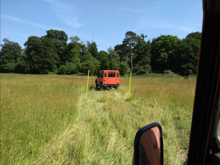 Orange Land Rover Defender driving through the blindfold driving tracks at Orangeworks Adventure Zone at Carton House