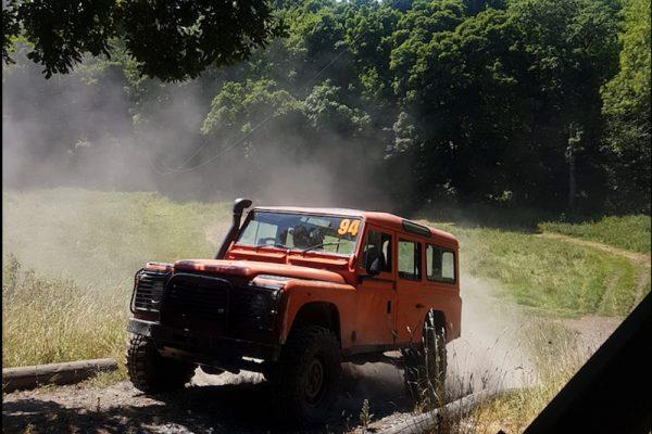 Orange Land Rover Defender driving