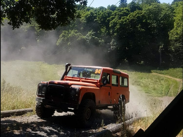 Orange Land Rover Defender driving the 4 x 4 off road tracks at Carton House.