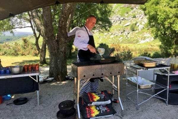 Our bushcraft chef Aidan cooking a wild BBQ lunch for a group of incentive delegates enjoying Orangeworks bespoke adventures