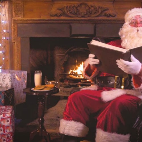 Santa Claus sitting by the fire reading