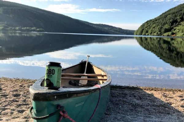 Wicklow Wolf Beer on a boat next to a lake