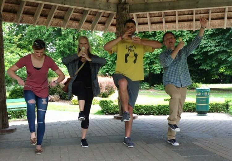 Delegates posing with one leg in the air for a photo challenge as part of the outdoor team building activity by Orangeworks