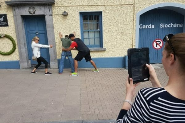 Team completing a photo challenge outside a Garda station as part of the tablet-based treasure hunt team challenge.