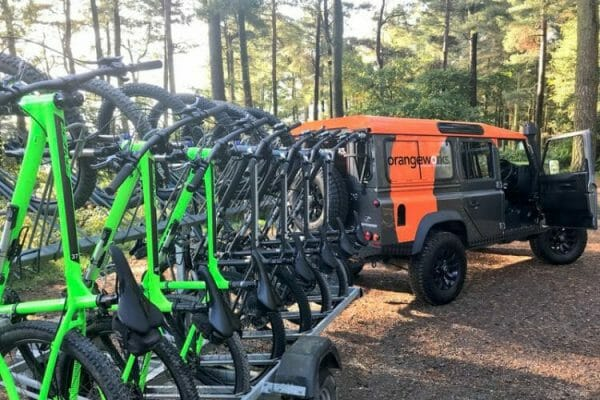 Green mountain bikes ready on a bike rack being pulled by a landrover for Orangeworks Mountain Bike Treasure Hunt.