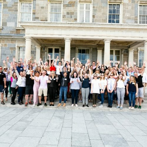 A team of delegates cheering and celebrating their completion of their group development activity with Orangeworks.