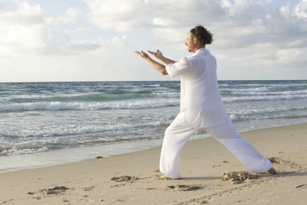 Man doing Tai Chi on the beach during team building experience.