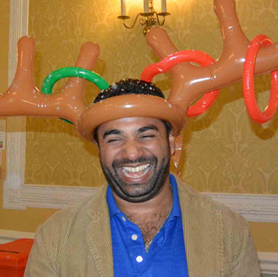 A participant of the fun christmas themed team activity Quickfire, wearing inflatable antlers on his head.