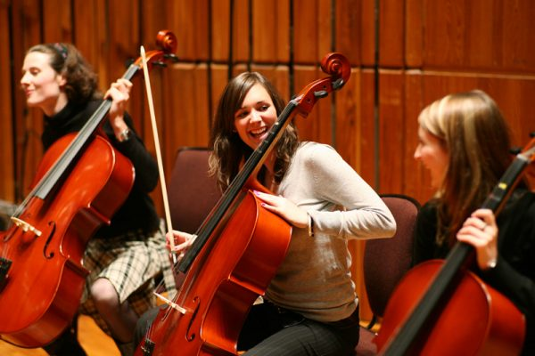 3 Cello players laughing together during the music-themed team bonding activity, Orchestrate, hosted by Orangeworks.