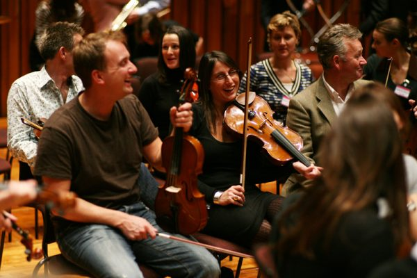 Team laughing while they learn how to play the violin for Orchestrate, one of Orangeworks fun team building activities.