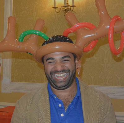 Laughing delegate wearing reindeer antlers during Quickfire Christmas, a fun corporate Christmas event idea.