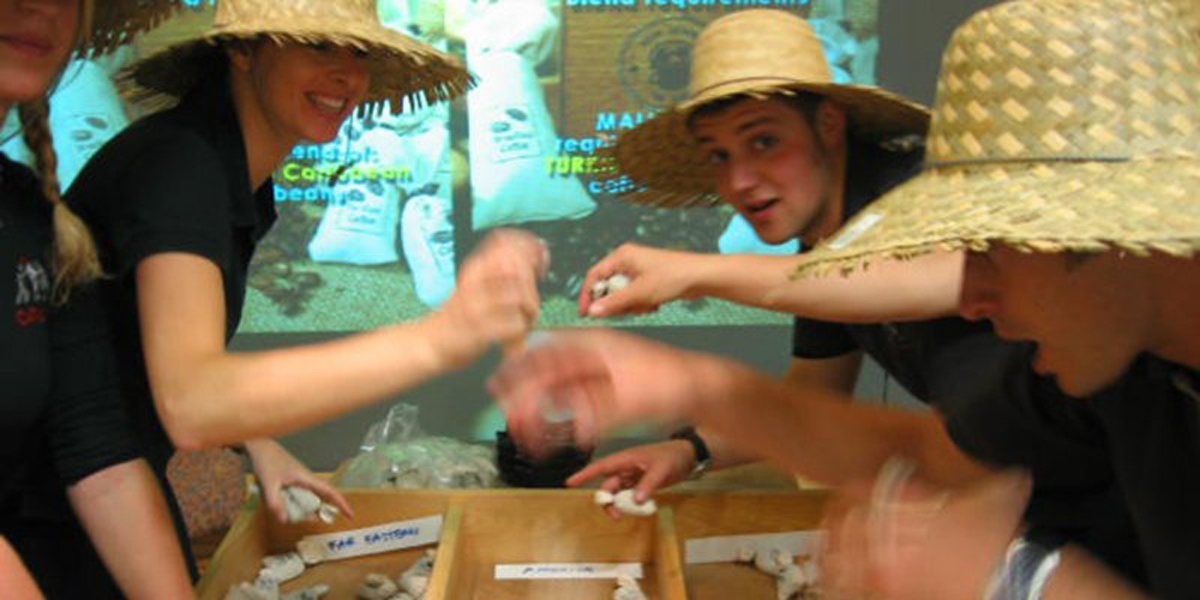Delegates wearing straw hands and trading coffee beans with each other during the high energy team building challenge.