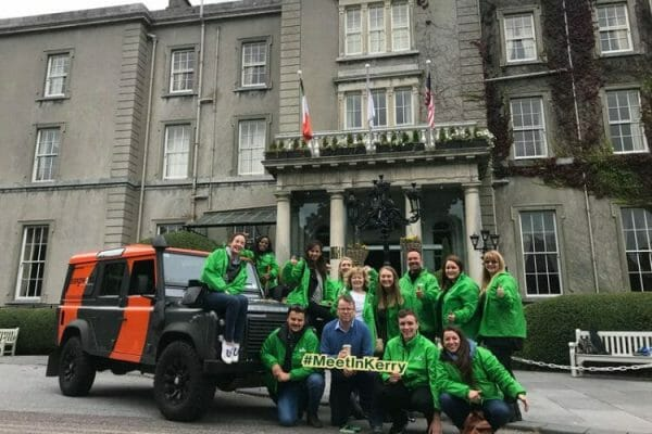 A team of delegates standing in front of a landrover as they get ready for the Go Team Killarney treasure hunt.