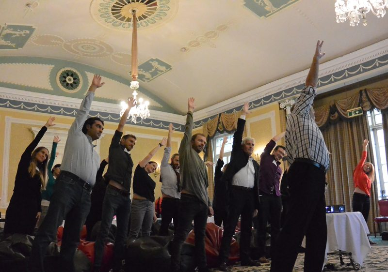 A team standing with their hand in the arm as they re-energise during Meditainment, a corporate wellness team building event.