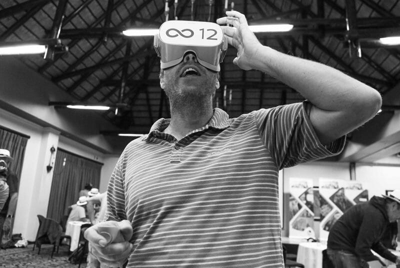 Delegate with a headset on playing the Infinite Loop. a virtual reality team building game.