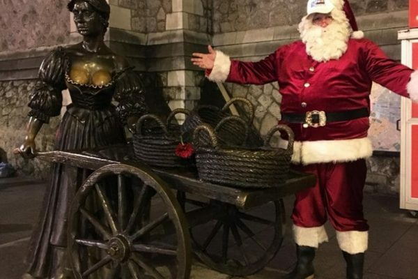 Orangeworks Santa Claus in the streets of dublin standing beside a statue during the team activity Go Team Hunt for Santa.